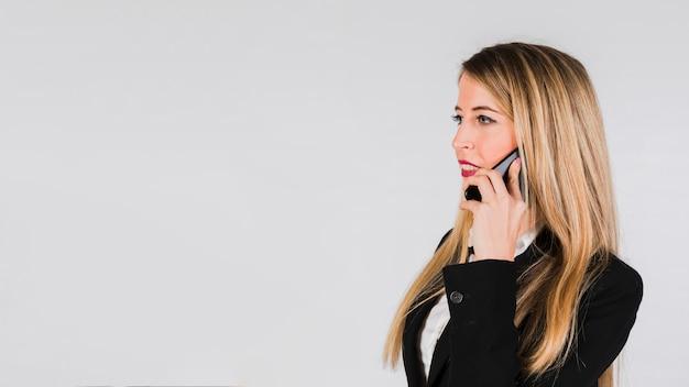 Schöne junge blondine, die am handy gegen grauen hintergrund sprechen Kostenlose Fotos