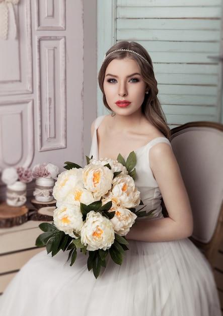 Schöne junge braut mit romantischem dekorationsrosa und -grün der blumen. holzkistenflaschen und unterschiedliche hochzeitsdekoration Premium Fotos