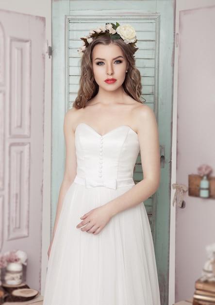 Schöne junge braut, wenn romantisches dekorationsrosa und -grün geheiratet werden. holzkistenflaschen und unterschiedliche hochzeitsdekoration Premium Fotos