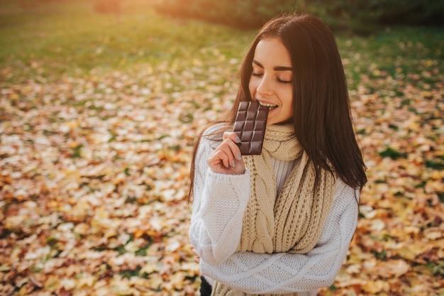 Schöne junge brünette, die auf einem gefallenen herbstlaub in einem park sitzt Premium Fotos