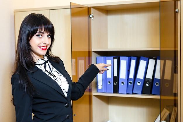 Schöne junge brunettefrau, die zu den ordnern mit dokumenten darstellt Premium Fotos