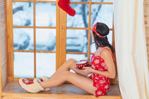 Schöne junge brunettefrau, welche die roten pyjamas am fenster nach hause sitzen trägt Kostenlose Fotos