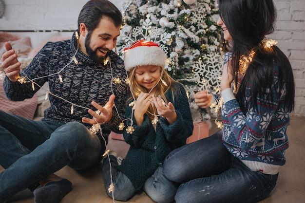 Schöne junge familie, die zusammen ihre ferienzeit genießt, weihnachtsbaum verziert, die weihnachtslichter anordnet und spaß hat Premium Fotos