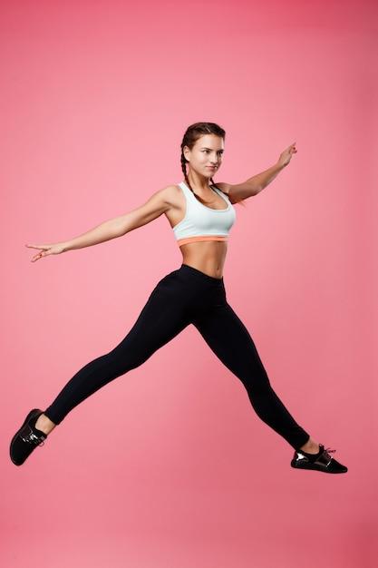 Schöne junge fitnessfrau in buntem top und schwarzen leggings Kostenlose Fotos