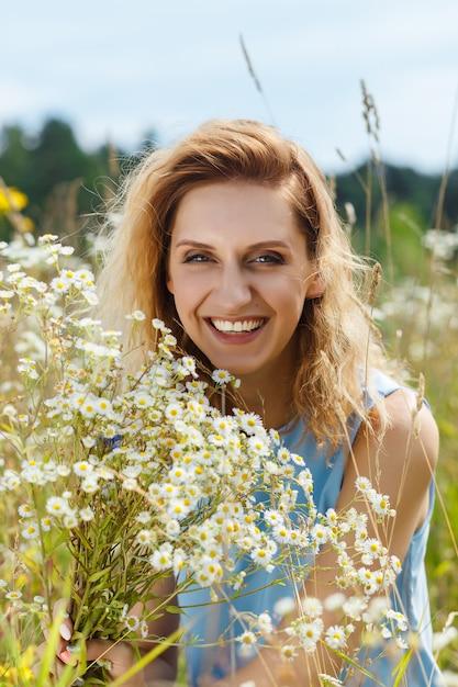 Schöne junge frau auf dem gänseblümchenblumenfeld Premium Fotos