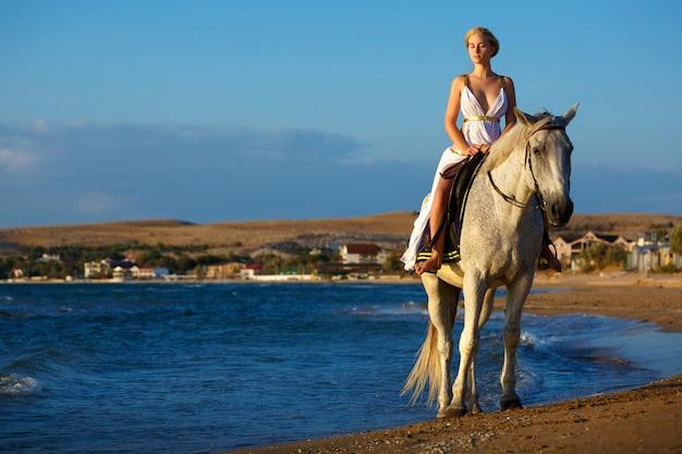 Schöne junge frau auf einem pferd in der nähe des meeres Premium Fotos