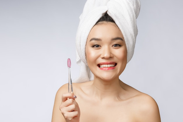 Schöne junge frau auf weißem getrenntem hintergrund hält eine zahnbürste, asiatisch Premium Fotos