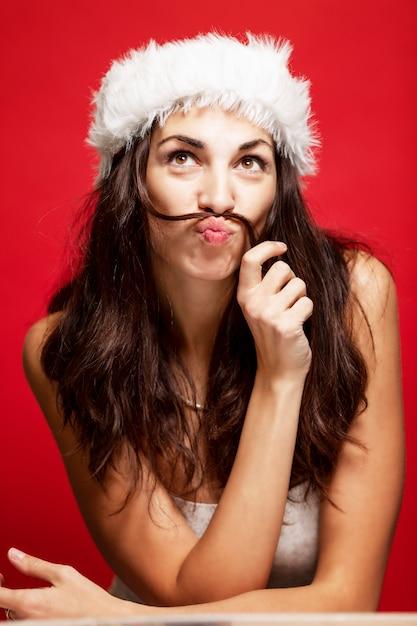 Schöne junge frau beim weihnachtsmann-hutlächeln. weihnachtsgeschichte. postkarte. vertikale. rot . Premium Fotos