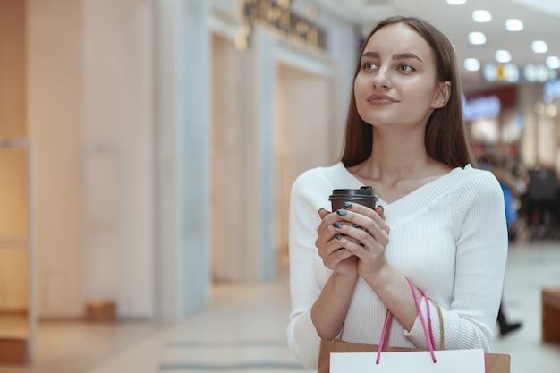 Schöne junge frau, die am lokalen mall kauft Premium Fotos