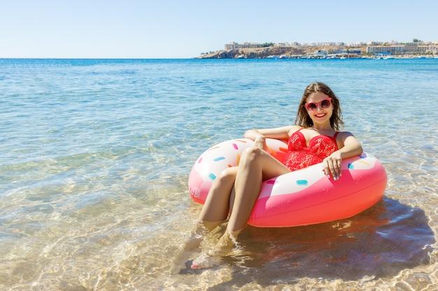 Schöne junge frau, die auf aufblasbarem donut im meer sich entspannt Premium Fotos