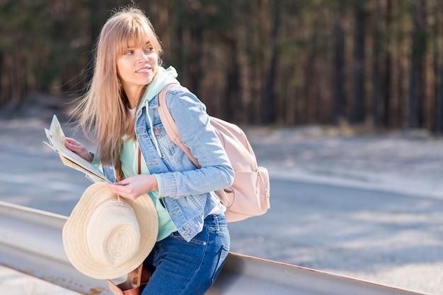 Schöne junge frau, die auf dem geländer hält die karte und hut weg schauen sich lehnt Kostenlose Fotos