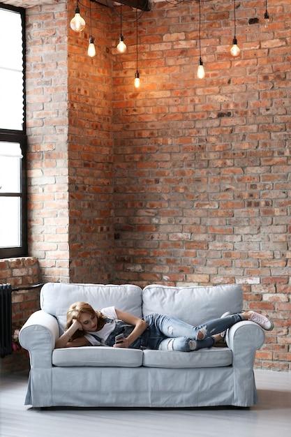 Schöne junge frau, die auf der couch, innenwohnzimmer ruht Kostenlose Fotos