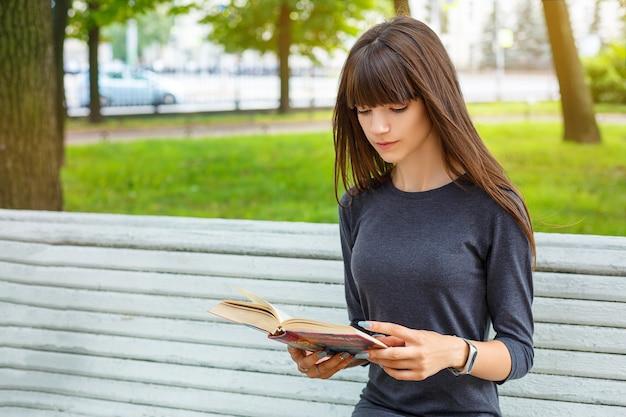 Schöne junge frau, die auf einer bank in der straße ein buch lesend sitzt. Premium Fotos