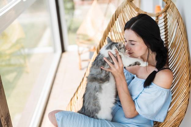 Schöne junge frau, die auf holzstuhl am patio liebt ihre katze sitzt Kostenlose Fotos