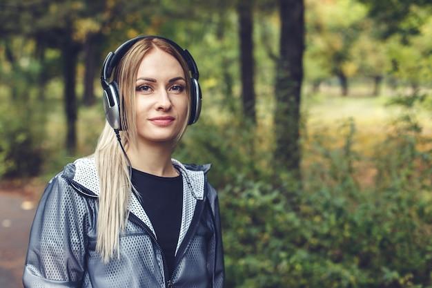 Schöne junge frau, die auf stadtpark, hörend musik auf kopfhörern geht. Premium Fotos