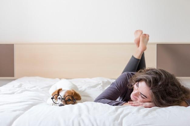 Schöne junge frau, die außerdem auf bett mit ihrem netten kleinen hund liegt. zuhause, drinnen und lifestyle Premium Fotos