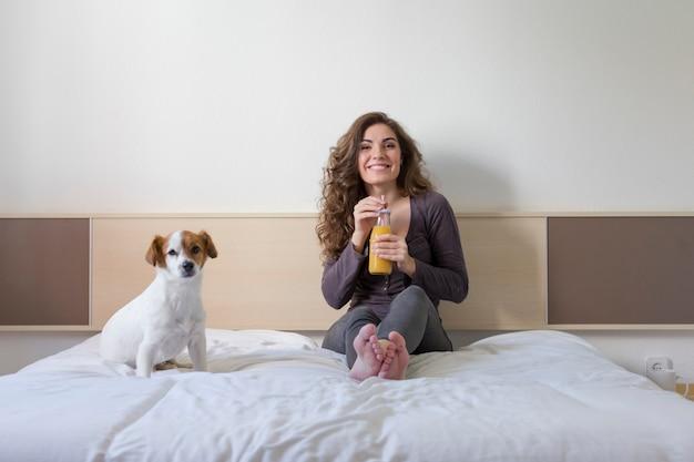 Schöne junge frau, die außerdem auf bett mit ihrem netten kleinen hund sitzt. Premium Fotos