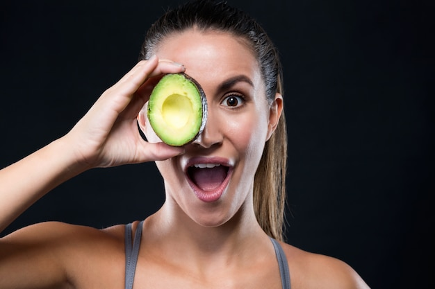 Schöne junge frau, die avocado über schwarzem hintergrund hält. Kostenlose Fotos