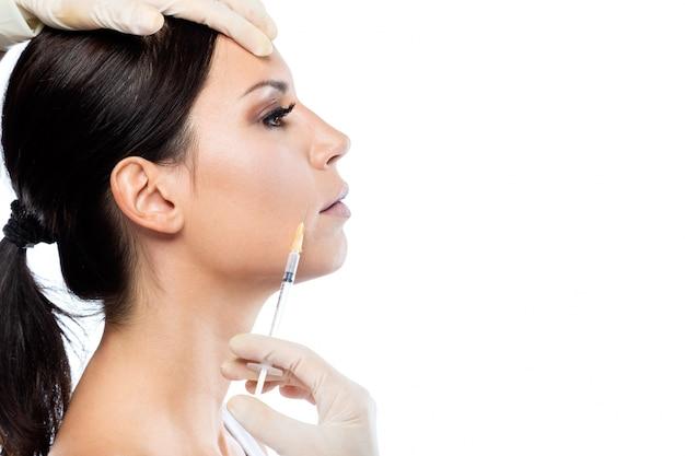 Schöne junge frau, die botox kosmetische einspritzung in ihrem gesicht erhält. Kostenlose Fotos