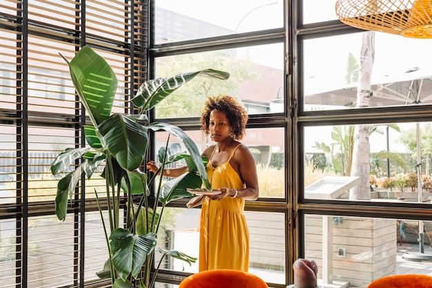 Schöne junge frau, die den teller steht nahe der grünpflanze hält Kostenlose Fotos