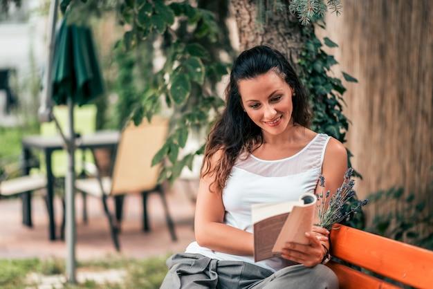 Schöne junge frau, die draußen ein buch auf der bank liest. Premium Fotos