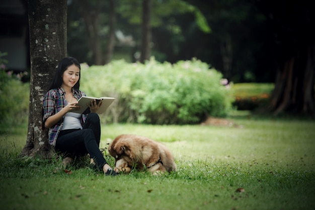 Schöne junge frau, die draußen ein buch mit ihrem kleinen hund in einem park liest. lebensstil-porträt. Kostenlose Fotos