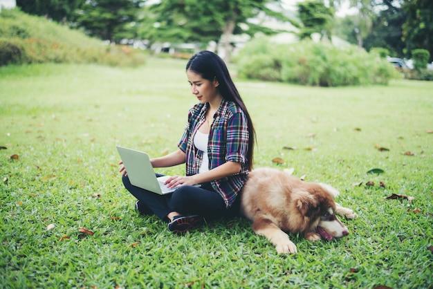 Schöne junge frau, die draußen laptop mit ihrem kleinen hund in einem park verwendet. lebensstil-porträt. Kostenlose Fotos