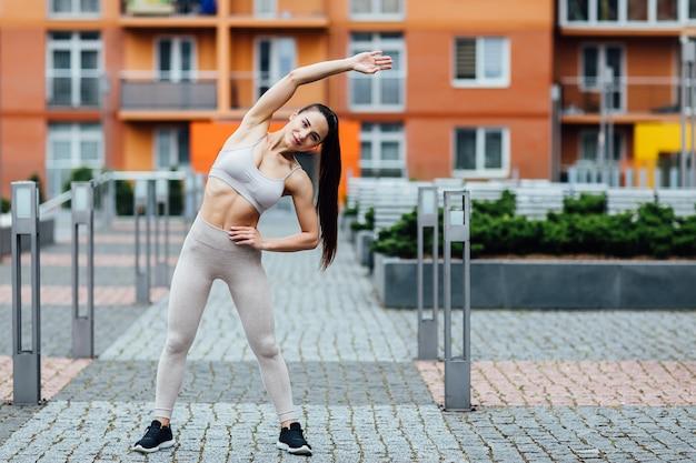 Schöne junge frau, die draußen übungen tut. wunderschöne fitness frau hart trainieren. Premium Fotos
