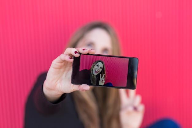 Schöne junge frau, die ein foto mit einem smartphone über roter wand macht Premium Fotos