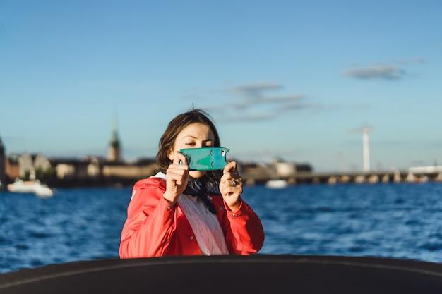 Schöne junge frau, die fotos auf einem smartphone macht Kostenlose Fotos