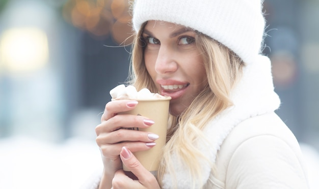 Schöne junge frau, die heißen kakao draußen trinkt. weihnachten. Premium Fotos