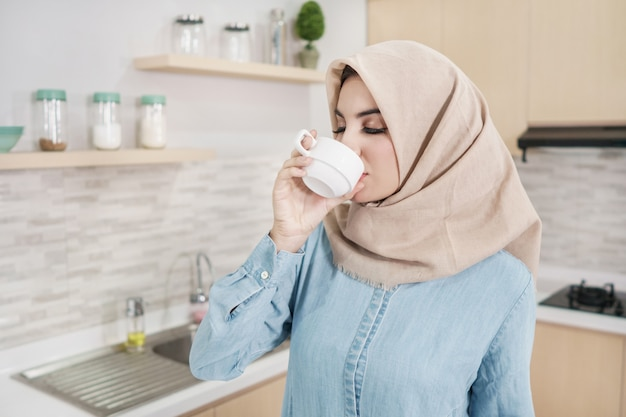 Schöne junge frau, die hijab trägt, der eine tasse kaffee trinkt Premium Fotos