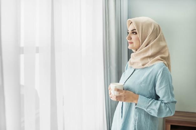 Schöne junge frau, die hijab trägt, während eine tasse tee trinkt Premium Fotos