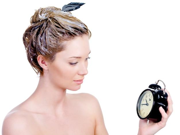 Schöne junge frau, die ihr haar färbt und auf uhr schaut - lokalisiert auf weiß Kostenlose Fotos
