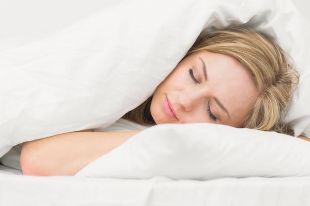 Schöne junge frau, die im bett schläft Premium Fotos