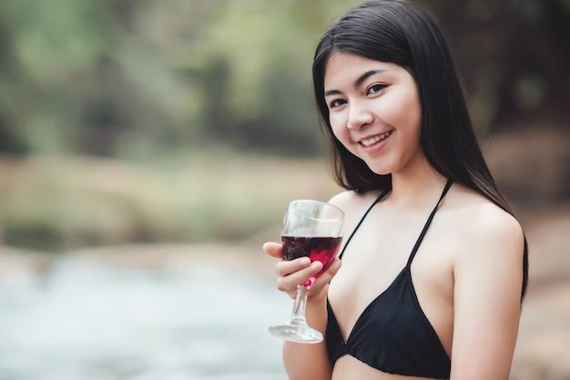Schöne junge frau, die im im freien trinkendes cocktail sitzt und den fluss aufpasst Kostenlose Fotos