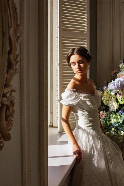 Schöne junge frau, die im weißen kleid nahe spiegel steht. Premium Fotos