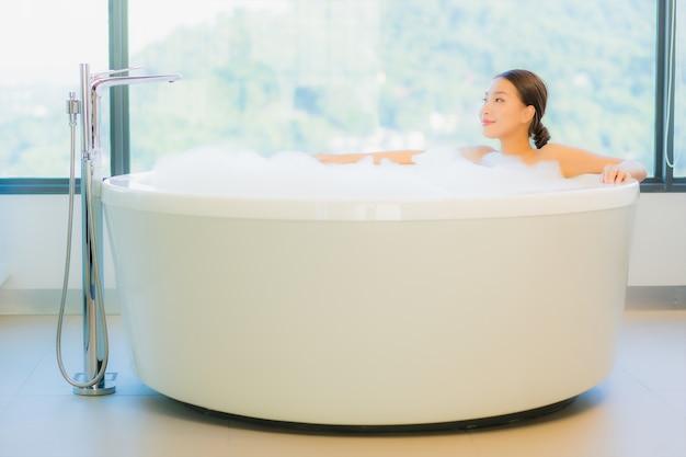 Schöne junge frau, die in der badewanne entspannt Kostenlose Fotos
