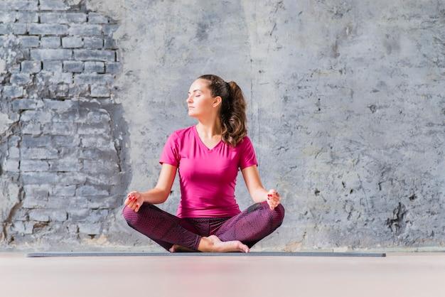 Schöne junge frau, die in meditierender yogaposition sitzt Kostenlose Fotos