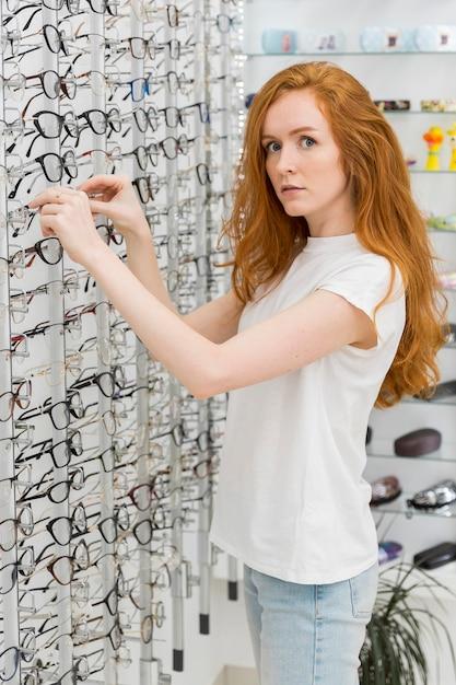 Schöne junge frau, die kamera beim entfernen von brillen von der anzeige im optikspeicher betrachtet Kostenlose Fotos