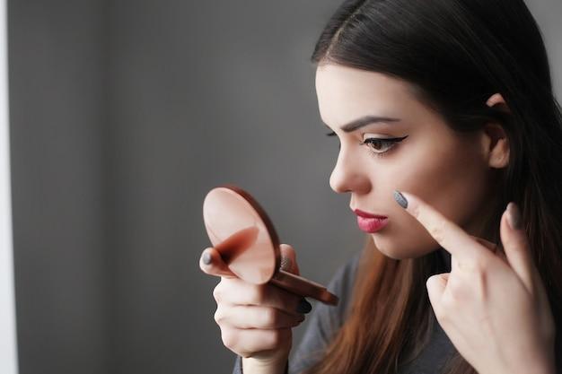 Schöne junge frau, die lippenstift auf lippen setzt Premium Fotos