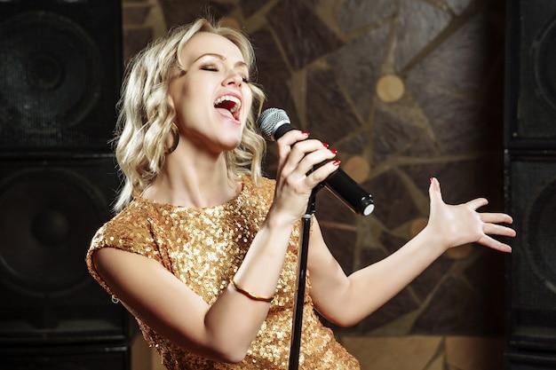Schöne junge frau, die mit dem mikrofon singt Premium Fotos