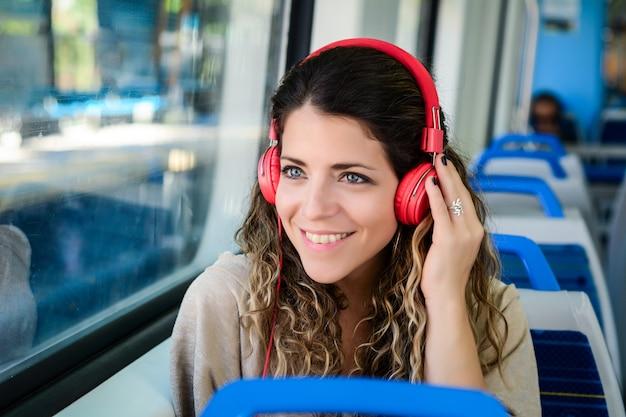 Schöne junge frau, die musik in einem zug hört. Premium Fotos
