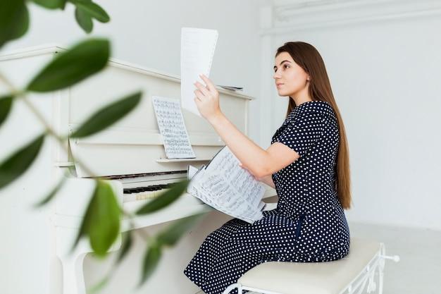 Schöne junge frau, die nahe dem klavier betrachtet musikalisches blatt sitzt Kostenlose Fotos