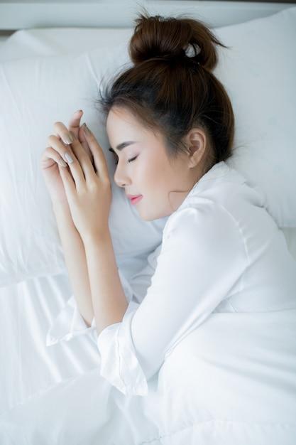 Schöne junge frau, die sich im bett hinlegt und schläft. Kostenlose Fotos