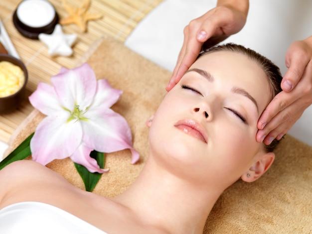 Schöne junge frau, die spa-massage des kopfes im schönheitssalon - drinnen hat Kostenlose Fotos