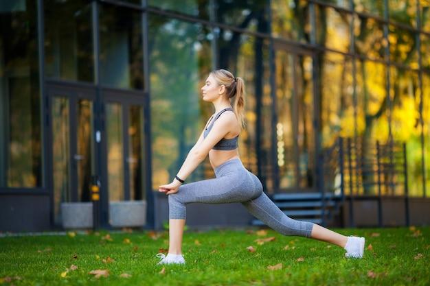 Schöne junge frau, die übungen im park tut Premium Fotos