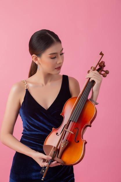 Schöne junge frau, die violine spielt Kostenlose Fotos