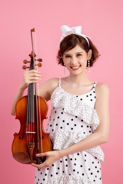 Schöne junge frau, die violine über rosa spielt Kostenlose Fotos