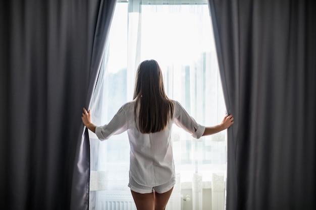 Schöne junge frau, die vorhänge öffnet und durch das fenster schaut Kostenlose Fotos